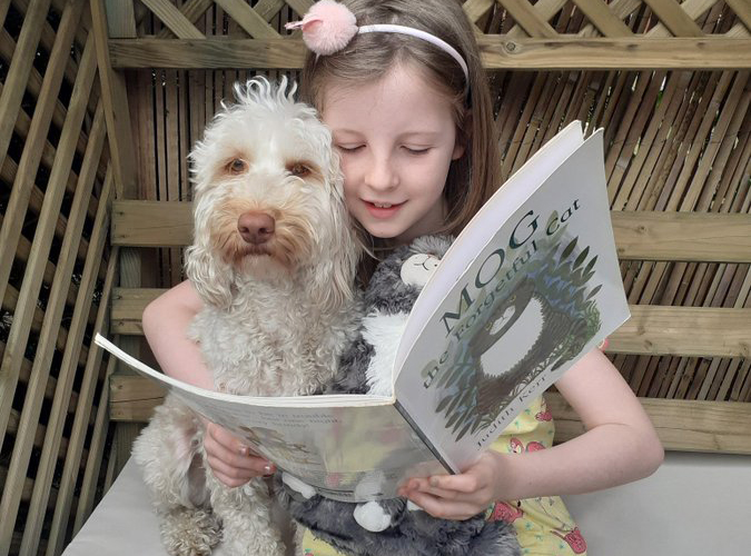 Girl reading Mog with her dog